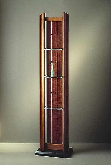Display Screen II by John Dodd. Display shelves with solid, curved lacewood frame, lacewood veneer slats, three glass shelves and a black granite base.