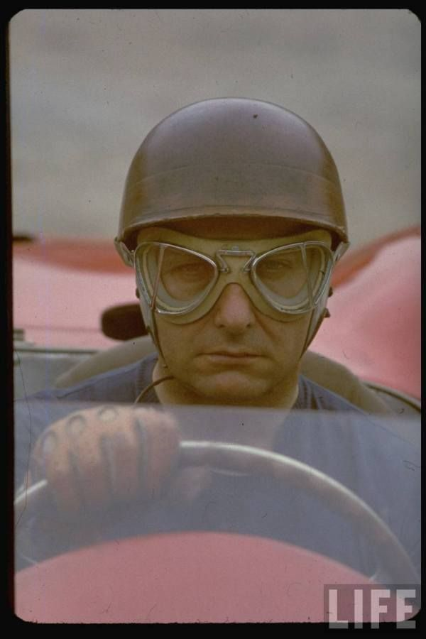 Argentine auto racing legend Juan Manuel Fangio sitting at wheel of race car at Le Mans -- 1967.