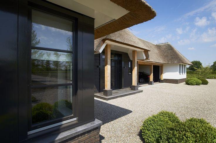 Idee voor boerenerf met inpandige garage en carports   Stijlvolle villa te Emst met zwarte kozijnen, natuursteen accenten en entree met eikenhout