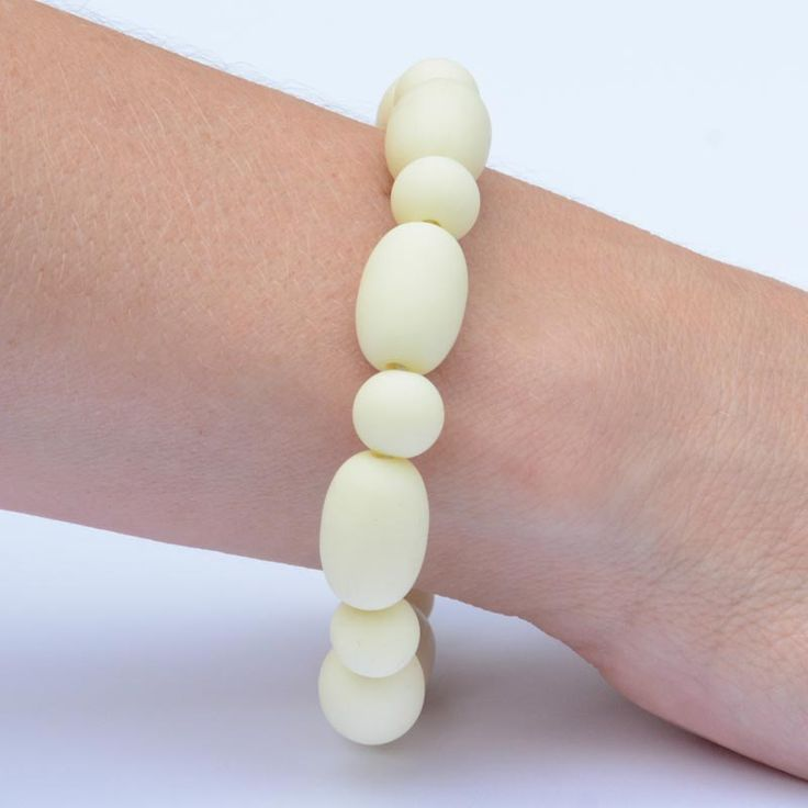 Oval range silicone teething bracelet for your baby to chew. This one in neutral bone.