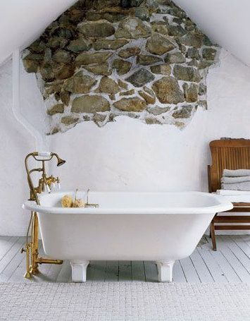 Exposed stone wall and chunky footed bathtub