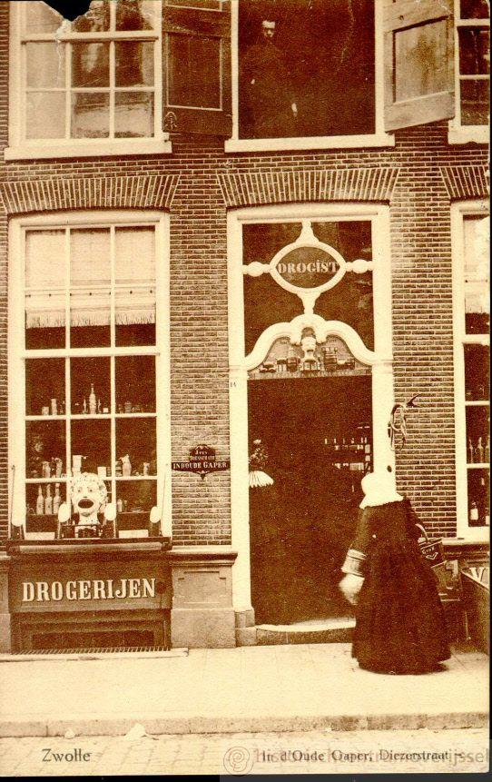 Diezerstraat 14, vrouw in klederdracht voor de deur van de drogisterij van J. ten Doesschate, genaamd 'In de Oude Gaper', ca. 1910. Links voor het raam de gaper en de houten suikerbroden. Aan de rechterdeurpost is een hertengewei bevestigd. De drogisterij was van 1782 tot 1990 gevestigd aan Diezerstraat 14. #Overijssel #Salland