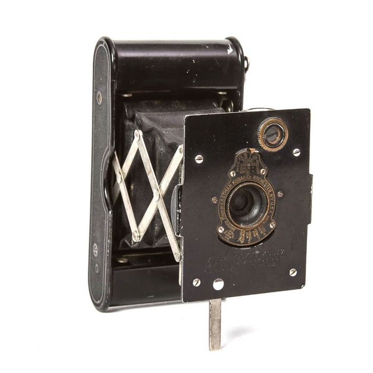 """A scarce antique Kodak Vest Pocket camera, one of the company's earliest models. The camera has a black painted finish. The lens has a black ring with raised gold tone lettering, marked """"Made by Eastman Kodak Co. Rochester, N.Y. U.S.A. – Pat. 1908 – Autotime"""". Just below the lens the camera is marked """"Vest Pocket Kodak – Patented Mar. 4 – 1902 – Other Patents Pending"""". The serial number is engraved on the hinged foot, """"80010""""."""