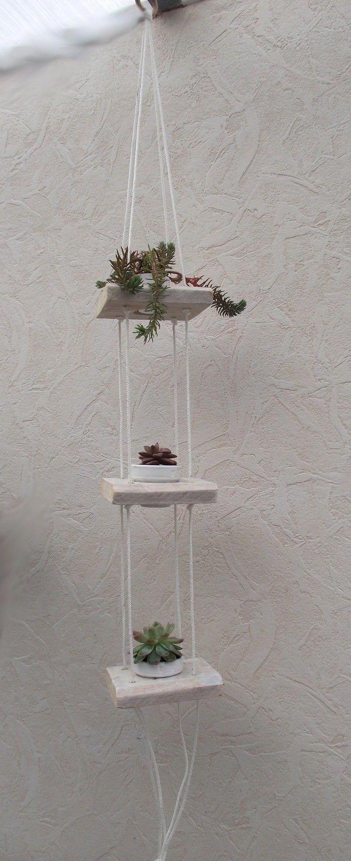 Suspension pour fleurs, faite avec du bois de palette, trois morceaux de 10cm sur 10cm avec un trou au milieu fait avec une scie cloche en fonction des petits pots. Dans les pots des plantes succulentes ,en haut Orpins des rochers (sédum), au milieu un crassula perforata,en bas une joubarbe gris bleuté.