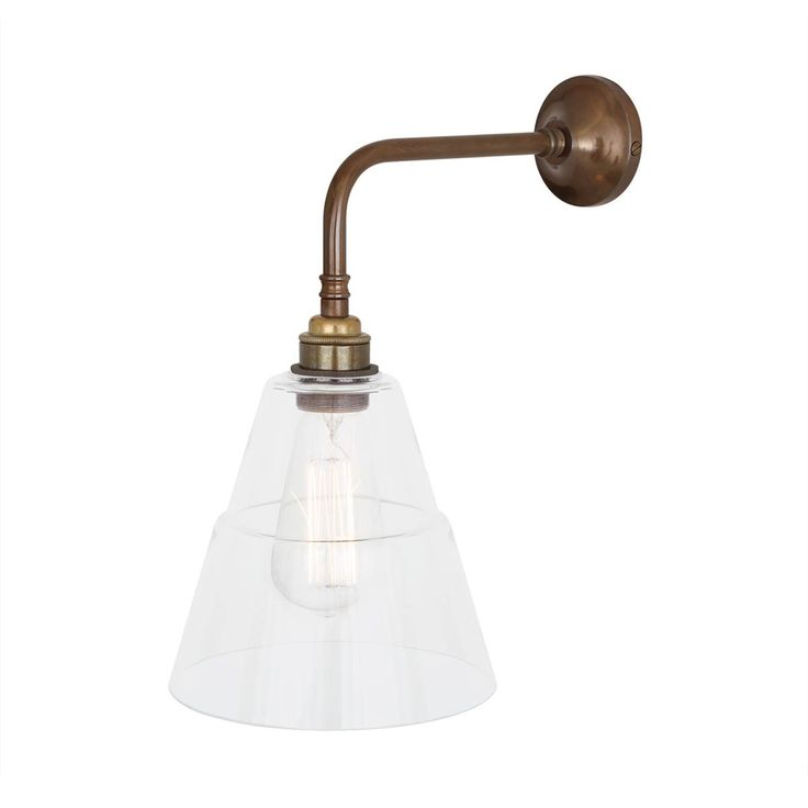 The Lyx is a modern wall light with a clear cone glass lamp shade.
