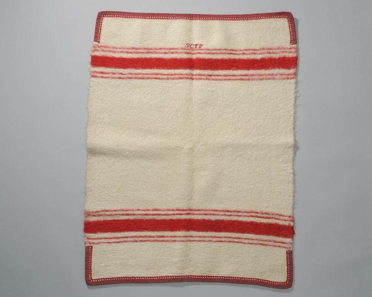deken, mogelijk bakerdeken, Marken, 1850-1940 Witte wollen babydeken met rode strepen, rode geborduurde initialen van de ouders van het kindje, afgezet met rood 'koor'. Wanneer men op Marken met een ingebakerd kindje uit wandelen ging gebruikte men over de groene deken vaak nog een witte met rode strepen die afgezet is met rood band. Mogelijk is dit een deken die op deze manier is gebruikt. #NoordHolland #Marken