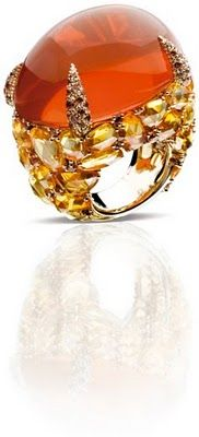 Pomellato, 18k natural white gold with a 66 karat oval cabochon fire opal, with flat rose and brilliant cut orange sapphires