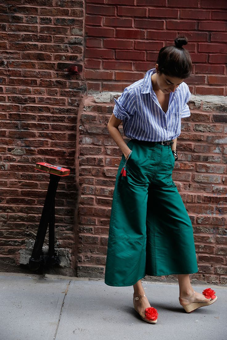 Striking and stylish attire created through pairing green culottes with a striped linen button down shirt and a black belt. Eye-catching shoes shoes complete the fashionable look.