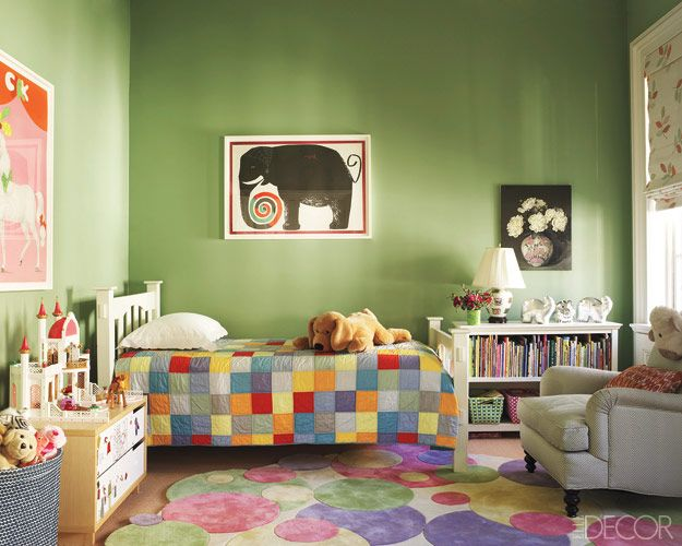 The bed and bookcase in the daughter's bedroom are by Pottery Barn Kids, the armchair is by Bridges, and the rug is by Roubini Rugs; the walls are painted in Farrow & Ball's Breakfast Room Green.