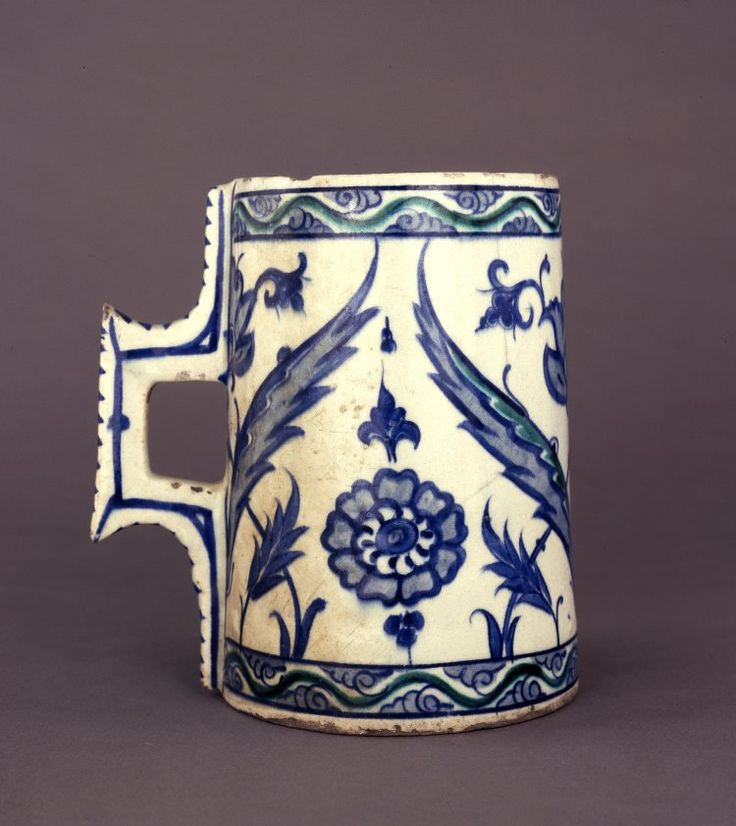 Vessel (humpen-shaped), tankard. Handle has stylised stitching.Undulating half palmette scrolls,saz leaves,medallions,rosettes,chinoiserie lotuses. Made of turquoise, cobalt painted and glazed ceramic, pottery.vessel; tankard; Ottoman dynasty; 16thC; Iznik