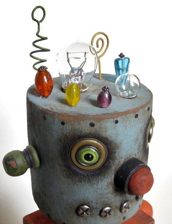 ~ Folk art robot assemblage ~ This vintage tin toy inspired robot was hand carved from wood, hand painted and antiqued for a vintage feel. Wire antennas, glass beads and light bulbs decorate his head. His eyes are painted washers and brads. Vintage finds, metal gears, curly wire and glass beads sit in a carved out area of his chest, which was then sealed in clear poured resin.  * 13.5 tall  * signed and dated  * one of a kind   To see more of my work visit me at www.gregguedel.com