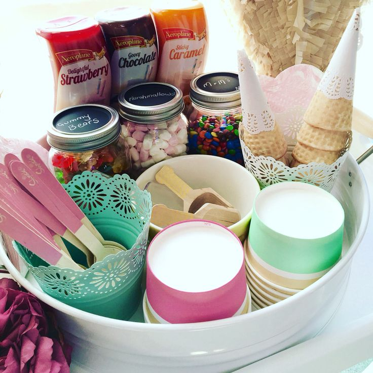 DIY ice cream Sunday station. Ice cream cups and spoons from discount store. Mason jars from Kmart filled with mini marshmallows , mini m&m's and gummy bears. Cottee's toppings are I great funky squirt bottles. Small paper doilies add some pretty to the waffle cones. Styling by D'lish Cupcakes & Accessories #icecreamparty