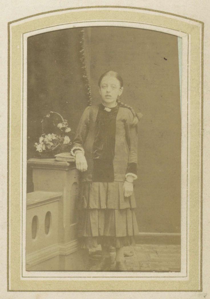 L.H. Serré | Portret van een jong meisje met een plooirok en een blouse bij een bloemenmand, L.H. Serré, 1870 - 1897 | Onderdeel van Fotoalbum van een Nederlandse familie met 168 cartes-de-visite en kabinetfoto's.