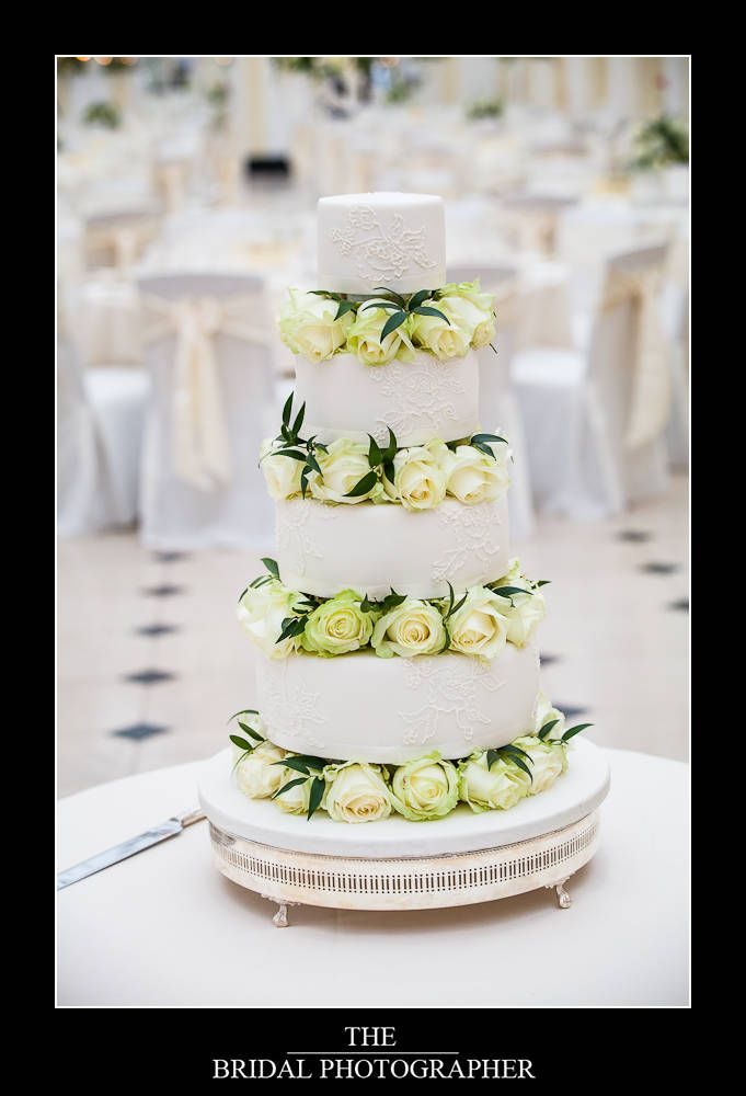 Ivory avalanche roses between the tiers of the cake in the Orangery at Blenheim Palace
