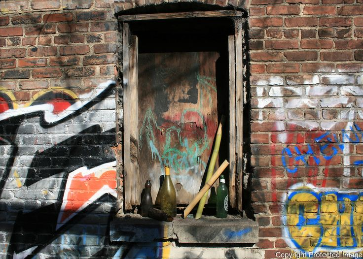 Grafitti wall with boarded window and assorted objects   J ...