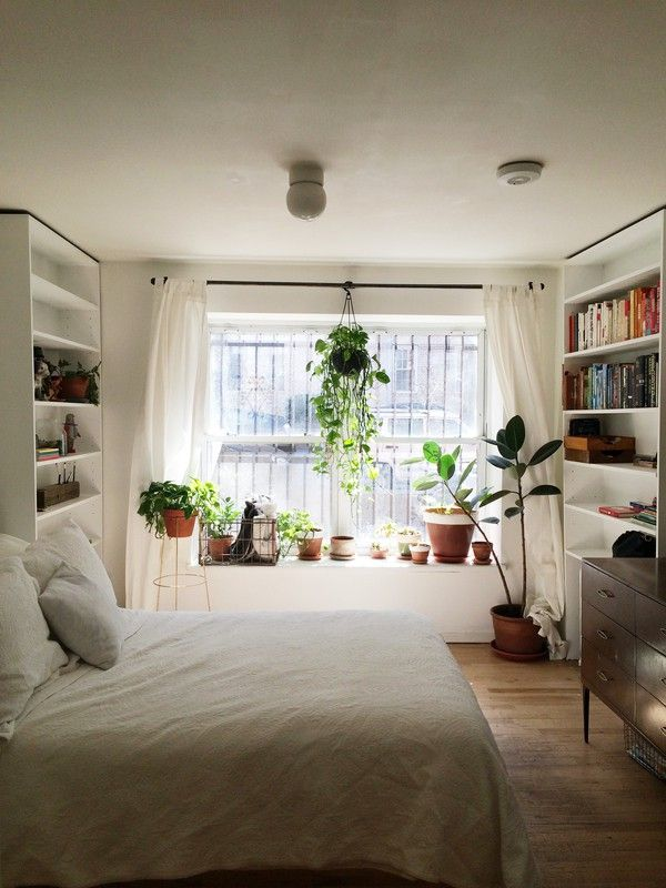 Give your sanctuary a touch of green by hanging your favorite plant from the curtain rod. It will get the sunlight it needs while adding a natural accent to your room. See more photos at Lovelyish.