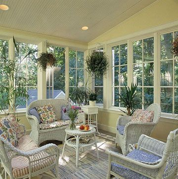 Cheery, yellow sunroom with beadboard ceiling detail.