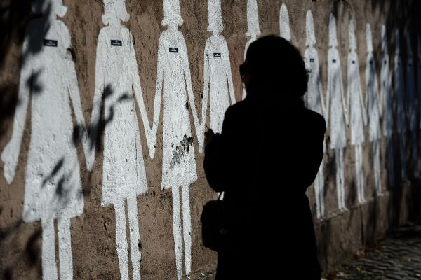 A woman walks past a wall displaying 107 figures with the names of the women who have been killed by men in Italy during the year as part as the International Day for the Elimination of Violence against Women on November 25, 2012.