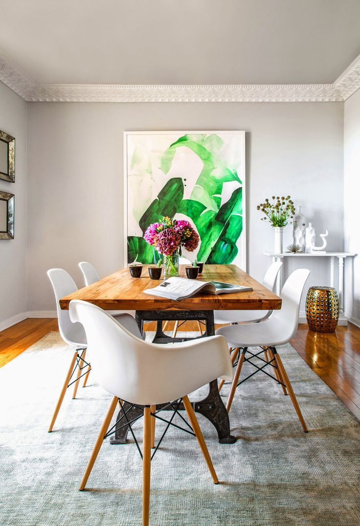 A modern dining space with eye-catching green art, flowers as centerpiece  and white