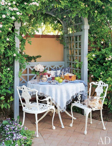 An outdoor dining area in the courtyard of Linda Ronstadt's Mediterranean-style house—which interior designer Christy Martin helped create in Tucson, Arizona—provides a shady spot for Sally Mae, one of the singer's three cats. (October 2004)