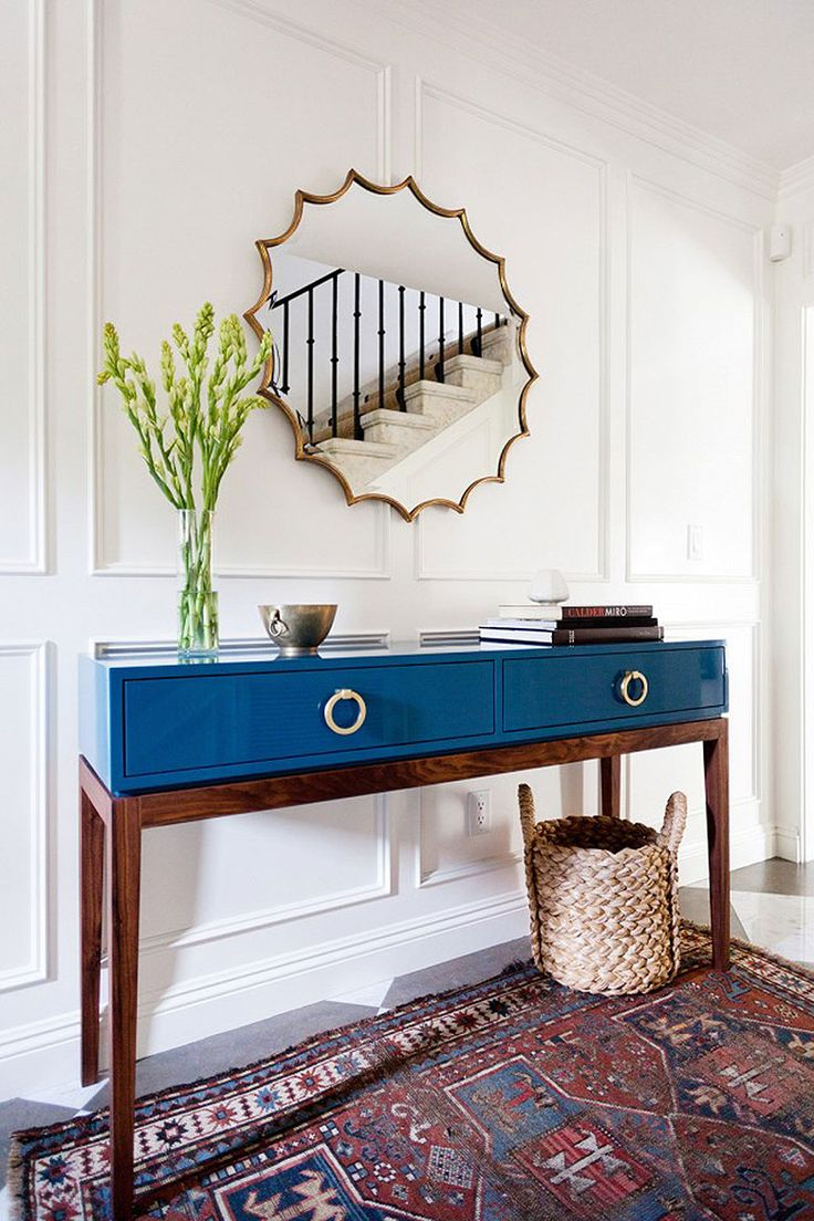 Modern entry with mid-century style table in blue lacquer finish, scalloped edged round mirror, white walls