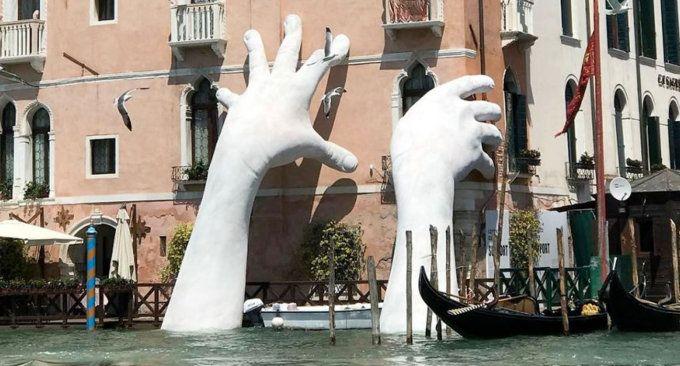 Due mani giganti escono da un canale a Venezia per sensibilizzare l'opinione pubblica sul cambiamento climatico
