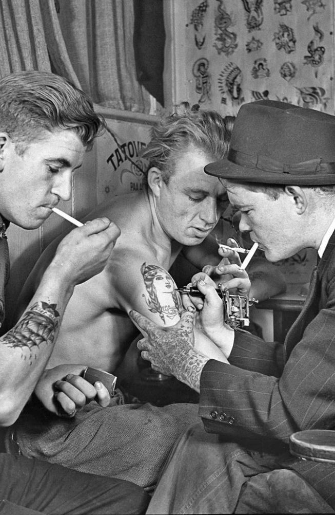 vintage photo. a group of 3 guys with tatoos smoking and drinking.