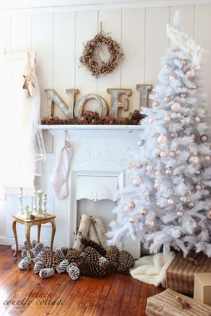 White Christmas decorating - white, natural and white tipped pinecones all together in pile by birch logs