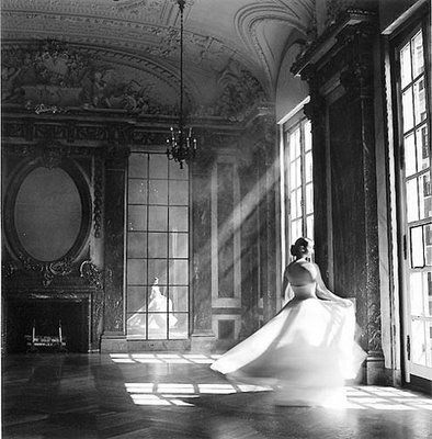Love this room with its long mullioned windows, ornately carved ceiling and fireplace surround AND that ballgown in motion. The black and white photograph and natural light make this scene luminescent and magical! Love the architecture & the way the model has swirled into the frame.