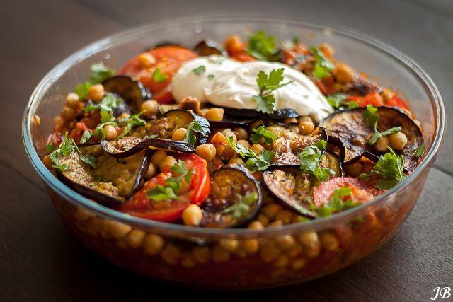 ngrediënten: - 2 aubergines - olijfolie - 1 grote ui, fijngehakt - 4 tenen knoflook, geperst - 400 g tomaten, in kleine stukjes gehakt - 1 el tomatenpuree - 6 middelgrote tomaten, in plakjes - 1 blik kikkererwten (400 g), uitgelekt - zout en zwarte peper uit de molen Voor de tahindressing: - 125 g Griekse yoghurt - 40 g tahin (Turkse winkel) - paar snufjes za'atar (naar smaak) - bosje platte peterselie (20 g), grofgehakt