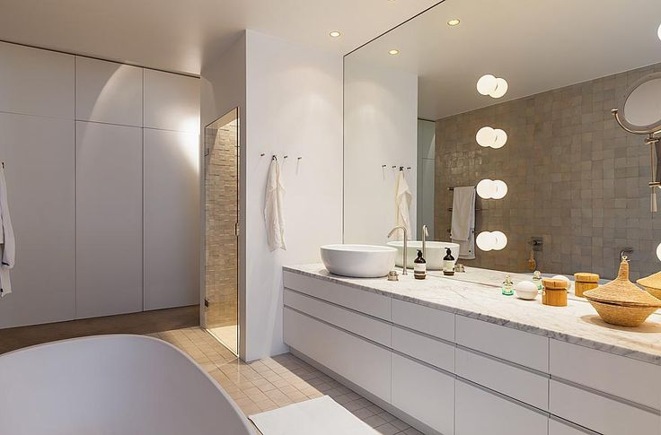 Home of Filippa K: Bathroom with huge mirror and a wall of cabinets.