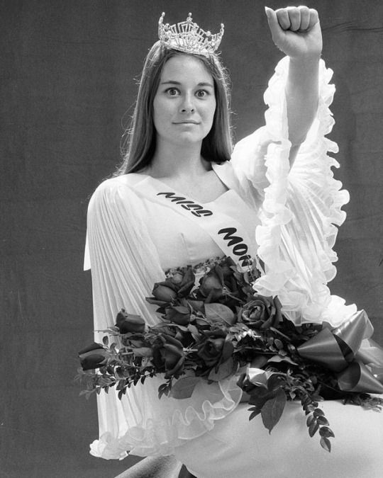 "From the Sep. 18, 1970 PARTING SHOTS: FOR AN ABDICATED QUEEN - ""In the bold spirit of Madison, LIFE awards one orchid—to be tucked away among all those roses—to dark-haired, strong-fisted Kathy Huppe, 18, who was elected this year's Miss Montana and shortly thereafter found herself barred from Atlantic City. Kathy balked when contest backers asked her not to take part in any political demonstrations. They found her opposition to the war in Vietnam to be contrary to everything that Miss…"