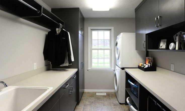 Mullet Cabinets: Narrow galley style laundry room with black cabinets and light countertops. The laundry ...