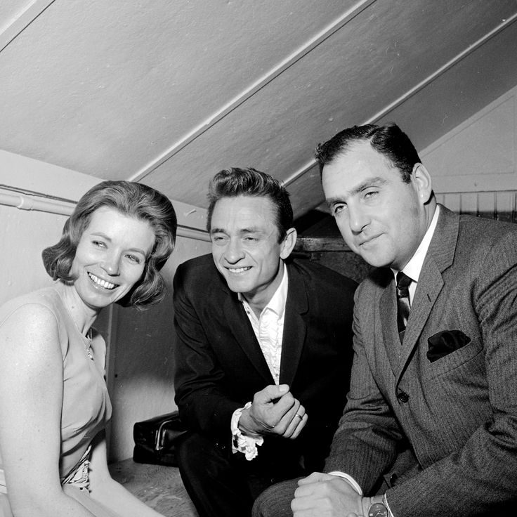 June and Johnny Cash with manager Saul Hollif in 1954.Hollif was Johnny manager from Feb11,1954 to 1973. In this photo Johnny performing  in London at London Arena