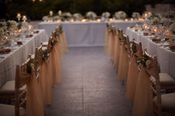 Wedding chairs wrapped with romantic gold fabric and little flower bouquets to add an elegant touch to the reception.