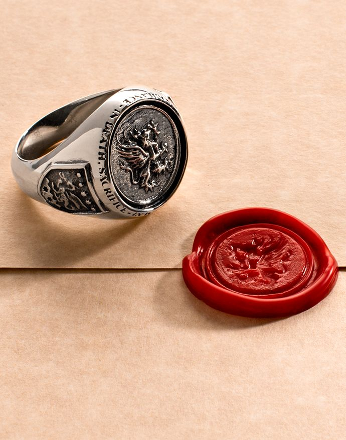 An image of the ring. It features a griffon in the center, with the Warden's oat circling the heraldry. The image also shows the imprint of the seal on hot wax, which leave the impression of a griffon.