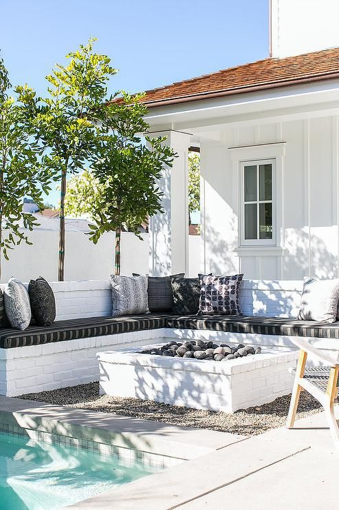 Chic patio features an L shaped white brick bench lined with black and white cushions facing a white brick fire pit and an in ground pool.