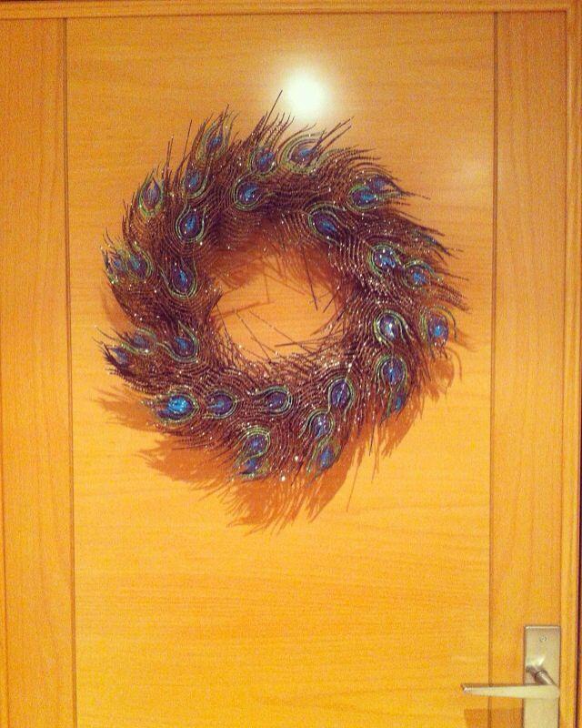 Corona navideña de plumas de pavo real