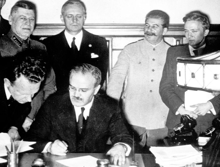 Soviet premier Josef Stalin (second from right), smiles while Soviet Foreign Minister Vyacheslav Molotov (seated), signs the non-aggression pact with German Reich Foreign Minister Joachim von Ribbentrop (third from right), in Moscow, on August 23, 1939. The man at left is Soviet Deputy Defense Minister and Chief of the General Staff, Marshal Boris Shaposhnikov. The nonaggression pact included a secret protocol dividing eastern Europe into spheres of influence in the event of a conflict.