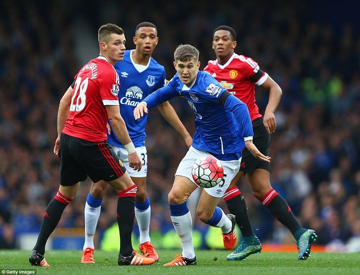 Everton and England defender John Stones races to recover the ball as Schneiderlin watches on during a comfortable win for United
