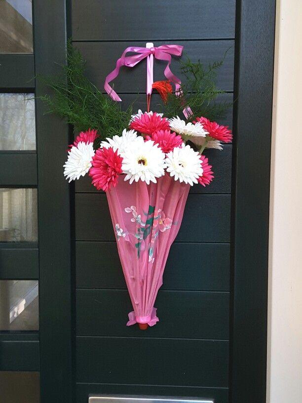 Paraplu gevuld met bloemen aan de deur  Kinderparaplu, kunstgerbera's erin, lint eraan vast en.........klaar!!