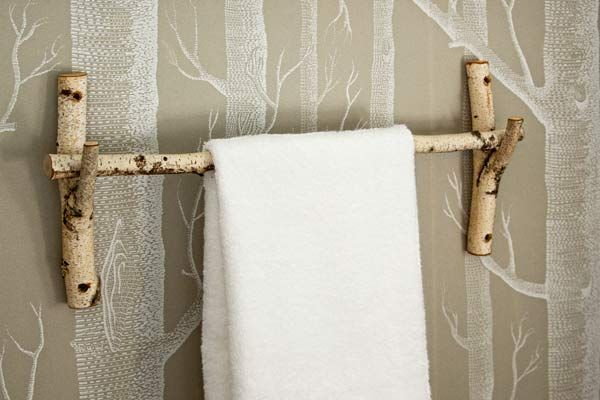Rustic towel bar DIY idea looks great in front of the tree wallpaper that home owner Jane Ackerman has in her Vermont home. The birch branch is super.