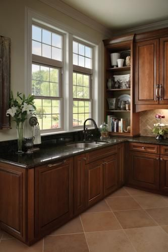 Tan single hung windows with grids  add a traditional feel to the kitchen. Featuring Tuscany Series single hung windows with colonial grids and picture windows above