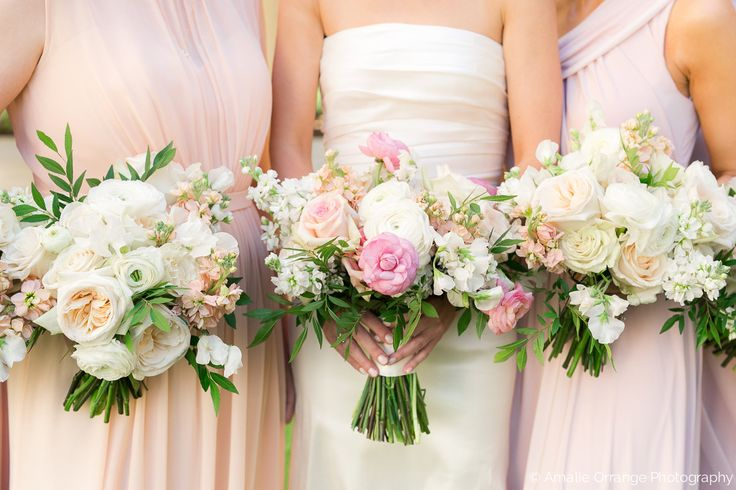 bride and bridesmaids traditional and slightly loose bouquets of white o'hara garden rose, white ranunculus, light pink ranunculus, peach stock, white stock, vendela rose, sophie rose, white sweet pea and elm greenery.