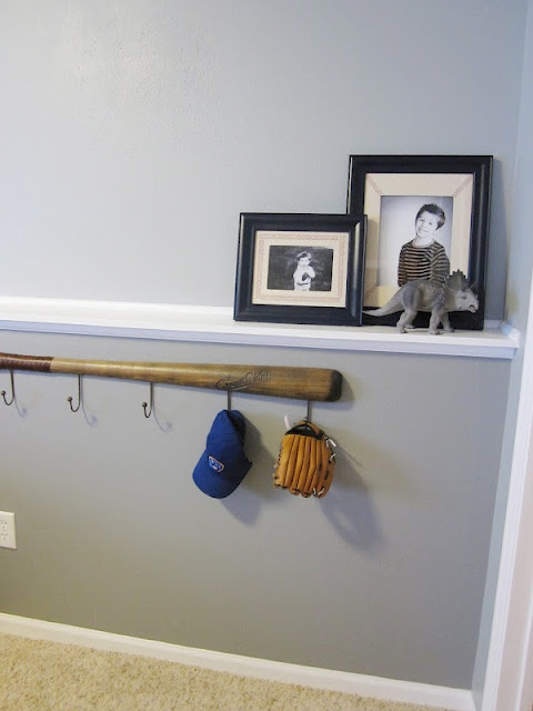 baseball hooks in back hallway with black shelf above and baseball pics of boys