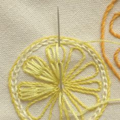 Citrus Slices: 1) stem stitch an outer circle; 2) chain stitch just inside the stem stitch; 3) stem stitch 8-10 segments, evenly spaced in the circle; 4) starting from the point of each segment, stitch two long chains on the LHS, finishing just inside the top edge, repeat this on the RHS, then fill the middle with additional chain stitches; and 5) complete all the segments in the same manner. Note: that there are three tones of a single colour for each slice.