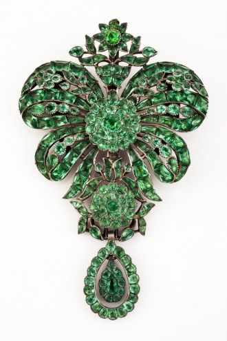 Devant de Corsage    Silver with green paste  Composed of four independent pieces: the first designed as a bow with central flower head, the middle element designed as another flower head surrounded by flowers and leaves, the lower part designed as pear-shaped pendant  Original hoop and pin of later date    Portugal, last quarter of the 18th century