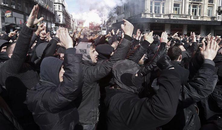 """Con consignas como """"estamos en casa"""", los manifestantes —rigurosamente vestidos de negro, una estética que se asemeja a la de muchos grupos ultraderechistas— han golpeado a varios traseúntes antes de que llegasen las fuerzas de seguridad. No faltaron los saludos nazi y las cervezas en mano de los ultra.  OLIVIER HOSLET (EFE)"""