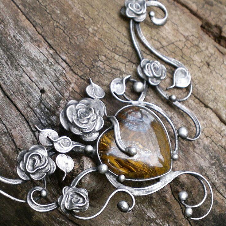Gothic Rose (tygří železo) Náhrdelník z tygřího železa zdobeného cínem technikou Tiffany a drátem.Patinováno,ošetřeno antioxidantem,leštěno,broušeno. Přívěsek o velikosti 12 x 8 cm je zavěšen na řetízku v barvě gunmetal se zapínáním na karabinku,délka - obvod cca 47 cm. Tygří oko - kámen ochrany,přitahuje bohatství,potlačuje deprese,zlepšuje náladu,podporuje ...