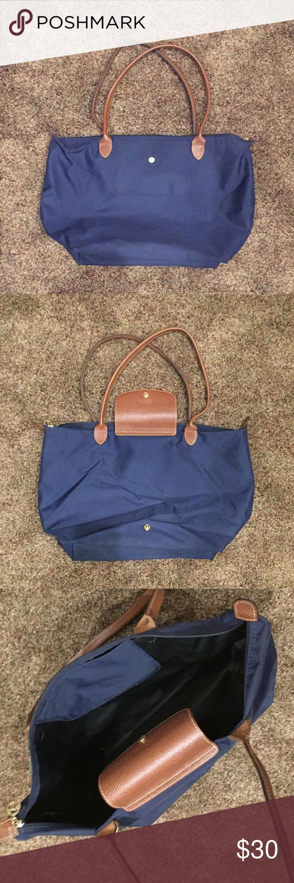 Navy Longchamp Bag Large Used, shows signs of wear. Light scratches and small holes at bottom corners (like Long Champ bags typically get). Still in good condition. Longchamp Bags Shoulder Bags